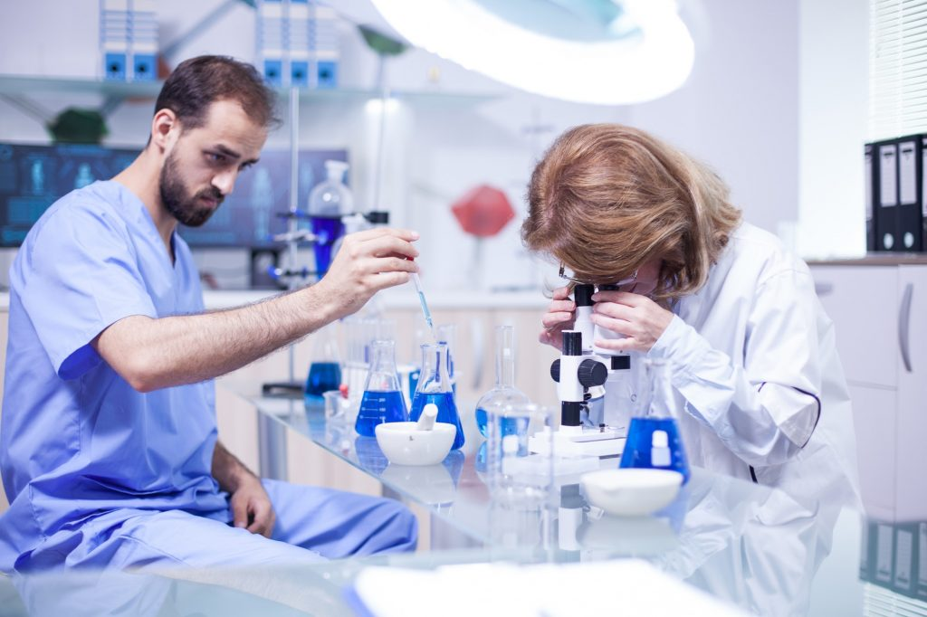 Young caucasian male scientist using a pipette analyzes a liquid to extract molecules in test tubes